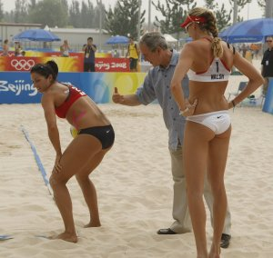 President Bush gestures toward the back of Misty May Treanor as he visits the practice of the U.S. beach volleyball team the 2008 Summer Olympic games in Beijing, China Saturday, Aug. 9, 2008. At right is Treanor's teammate Kerri Walsh. (AP Photo/Gerald Herbert)
